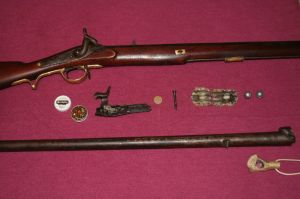 The refinished Brunswick rifle is shown with fired patches and the lock and barrel from the author's original gun. The hand lens was used to inspect the barrel between shots for signs of gas leakage.