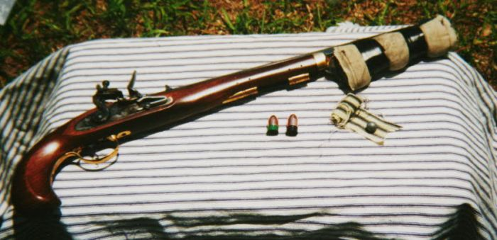 "Pedersoli Bounty .50 caliber flintlock pistol with ""saddlebags"" and loading components."
